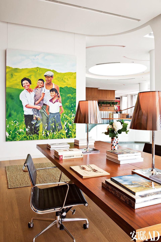 以男主人小时候的一张家庭合影为蓝本,请艺术家专门创作的大幅油画,为整个家带来浓浓亲情。开放式书房位于三层,墙上的油画出自艺术家景柯文之手。书桌上的花瓶来自BoConcept北欧风情。金属台灯来自Flos。