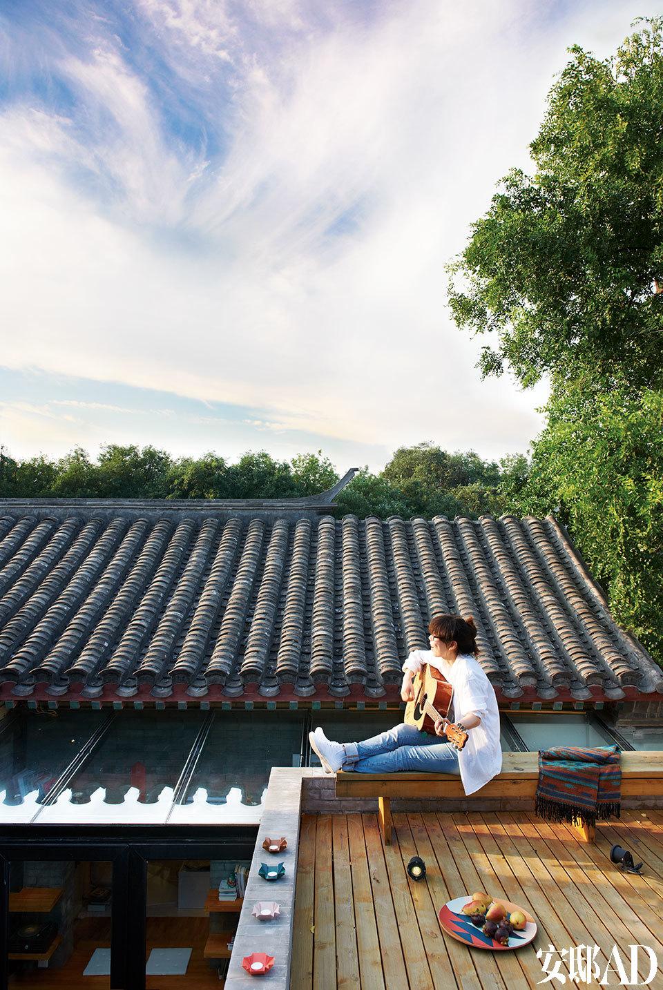 天朗气清的日子里,宝姐喜欢坐在露台上消磨时光。望着北京城的蓝天,随性弹上一曲吉他,也是很好的享受。彩色水果盘和小盘子,以及宝姐身后的披肩均来自BoConcept北欧风情。