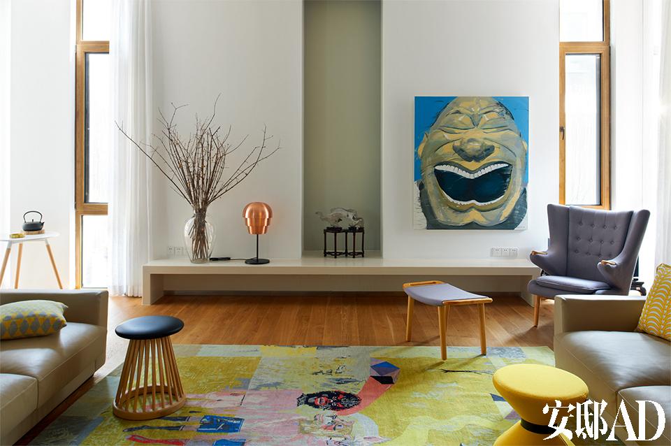 """设计师给家布置好一个舒适、合理的"""" 生活舞台"""",舞台上的精彩,还要靠一家人幸福演绎。 客厅中,一张由艺术家岳敏君创作的油画《笑脸》十分醒目,姜黄色艺术家合作款地毯来自Rugstar毯言织造,台灯是北欧设计,购自德国,沙发是汉森熊椅(Hans Wegner Papa Bear Chair),正中央的墙壁凹进处摆着一块太湖石,左侧近处的Tom Dixon木质坐墩来自家天地。"""