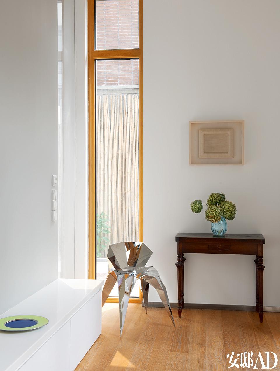 门厅处的装饰柜是20世纪30年代上海AreDeco风格的古董家具,购自上海,颇具未来感的镜面不锈钢单椅是艺术家张周捷的作品。
