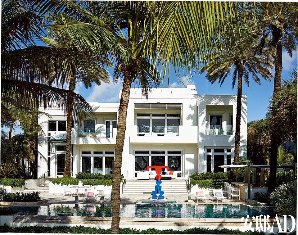 房屋背面的外观。游泳池畔立着Keith Haring设计的雕塑,还配备着Richard Schultz设计的Knoll座椅。地面由Ann Sacks的凝灰石铺成,游泳池和温泉浴缸均由Bisazza瓷砖做内衬。