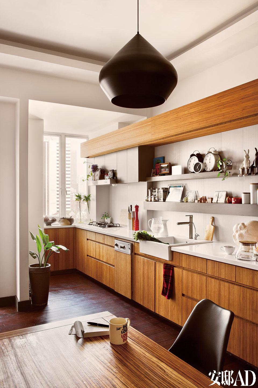 明亮干净的白色与木色,很好地解决了厨房白天光线不足的问题。调味料和餐具都被整齐地收纳在柜子里,同时也释放出厨房架上的空间,好让两人摆放收集自各处的新奇玩意儿。