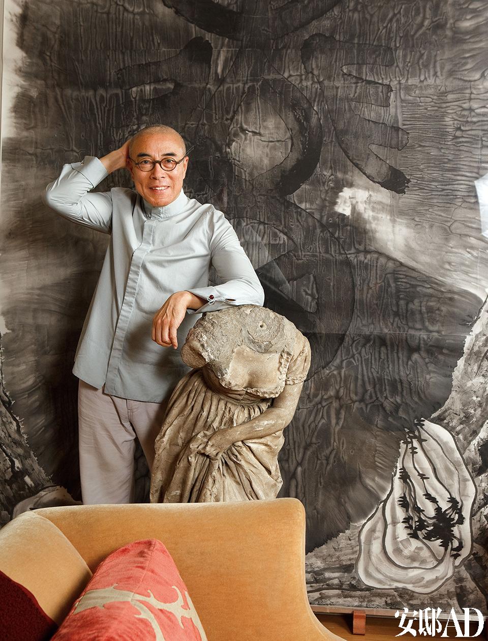 """男主人: 谷文达,当代备受国际瞩目的华人艺术家之一。他1955年生于上海,上世纪80年代移居纽约,作品以大胆激进、惊世骇俗著称,其中名为《天坛》的作品登上1999年3月号的《美国艺术》,影响了之后的一批艺术家。谷文达现生活、工作于纽约和上海两地。谷文达在自己位于纽约布鲁克林的家中,背景的""""水墨画""""是那幅著名的《联合国》。"""