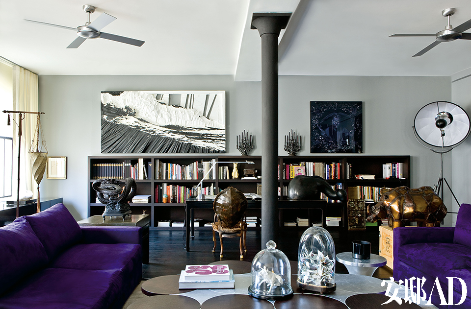 穿过门廊,便进入到宽敞的起居室。两组紫色丝绒大沙发来自Desio,中央的大茶几由Nicolas Hertrich和Marc Adnet设计,受著名的Tam Tam系列座椅启发,橡木制成。墙上挂着Erwin Olaf的摄影作品和Bernard Quesniaux的画作,柱子旁边有一张由Michel Hallard设计的玳瑁靠背座椅。