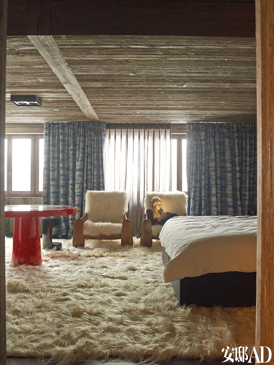 铺满地面和扶手椅的长山羊毛地毯显示出浓郁的北欧风情,窗帘和窗纱来自Jules et Jim Paris,红树脂片制成的桌子由Jean Brand设计,Atelier Janus出品。