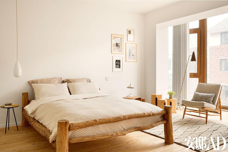 主人根据从家居杂志中的一幅图片,定制了这张双人床,原木的粗朴质感,带出一种林间度假屋的悠闲。一间卧室,充满原始气息的木床是定制品,床上用品来自West Elm;左侧的床边桌为Terrence Conran出品,来自伦敦的John Lewes;白色的Drop One Pendant吊灯由Btc出品。右侧的单人沙发是经过修缮和重新软包的中古产品,落地灯来自Fins de Siecles。