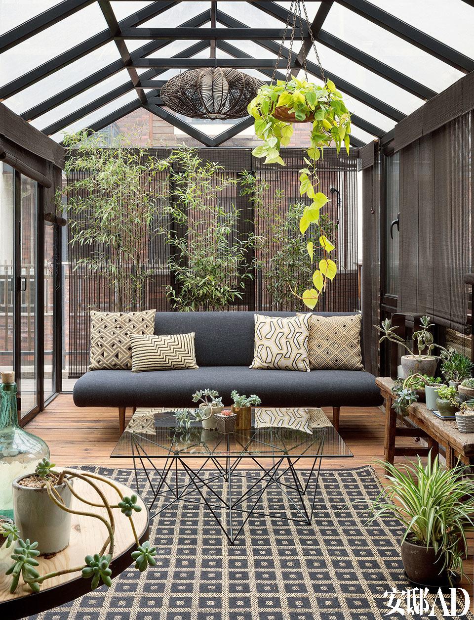 院子中,金属框架的玻璃阳光 房带来一座郁郁葱葱的室内花园,给家里增添了勃勃生机。设计师在院落中设计了这间阳光房,吊灯来自Pilma,户外沙发购自Heal's,玻璃茶几购自Habitat,地毯由Caravane出品。