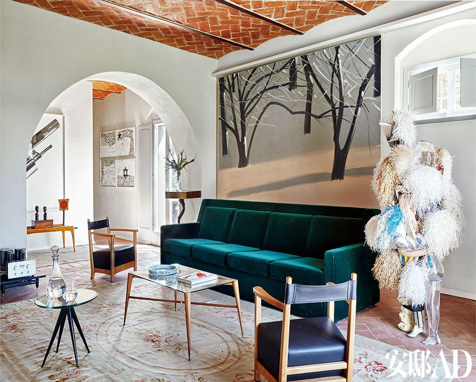 """老建筑有新房子无法比拟的魅力,不规整的线条反而给它带来有机的生命力!绿色天鹅绒沙发""""P17 Sant'Ambrogio""""和独立扶手椅样品""""P21 Chinotto"""",它们都是由 建筑师Luigi Caccia Dominioni设计、由意大利Azucena生产的。沙发前面是意大利设计师Paolo Buffa设计的20世纪40年代长方形茶几。黑色桌脚的圆形茶几是意大利设计师Pietro Chiesa (1892-1948)为Fontana Arte设计的家具之一。"""
