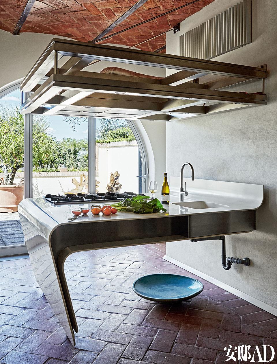 流线造型的厨房岛台好似一件艺术品,其实用功能又巧妙地令整个家不再冰冷。厨房集成了燃气灶台和带水龙头的水槽,并同时提供了一个很大的工作台空间。这是MdAA建筑公司量身定制的设计。