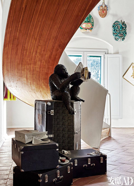"""在楼梯间下,摆着意大利艺术家Bertozzi& Casoni题为""""Pot Pourr""""i(2005)的作品。照片尽头的墙壁,大门的上方,挂着意大利艺术家Luigi Ontani (1998/2009)的作品Máscaras Musicales《音乐面具》。"""