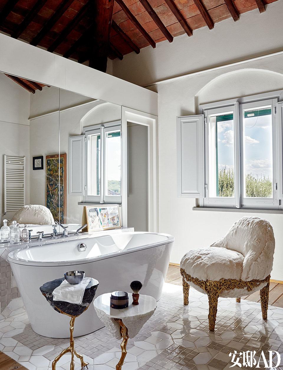 """浴室里,巴洛克风格的小边几和扶手椅都是巴西设计师 Campana兄弟的作品,其实用设计总是像艺术品般独一无二。浴室里巴洛克形状的小边桌与""""Roccocò""""扶手椅形成对比,边桌和扶手椅都是Campana兄弟2012年的设计作品。"""