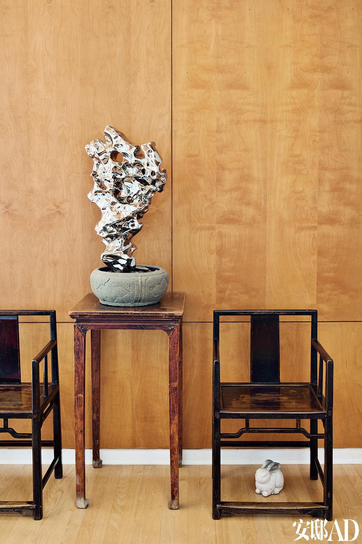 这是两把19世纪的中式玫瑰椅,中间是19世纪的中式马蹄腿方形花盆架,艺术家展望的不锈钢山石盆景,摆在花盆架上。中式家具营造的复古氛围里,当代艺术家展望的不锈钢雕塑成为神来之笔。