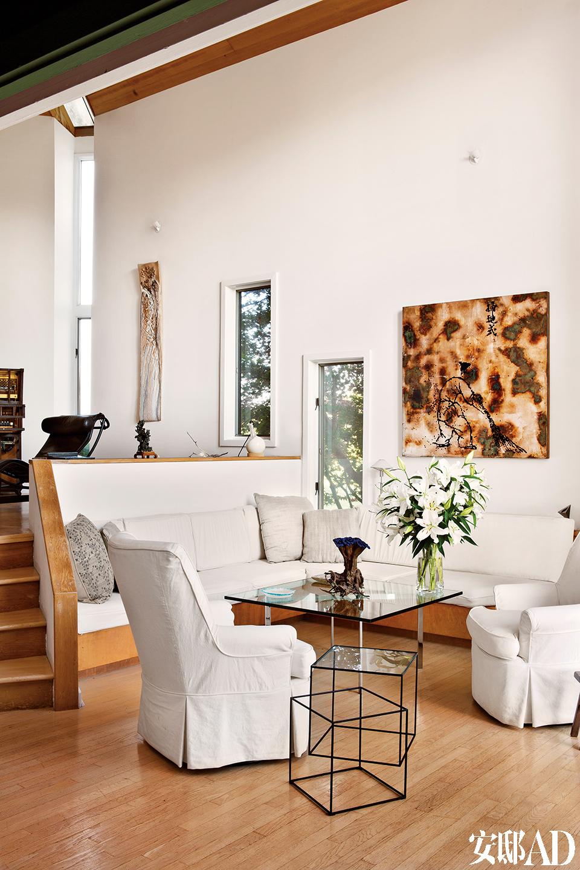 黑色边桌由Nendo设计,Capppellini生产制造。塞罗那咖啡桌是建筑大师密斯·凡·德·罗的经典设计,由Knoll生产制造。白色家具只为衬底,窗外的婆娑树影与墙上的艺术品互为呼应。