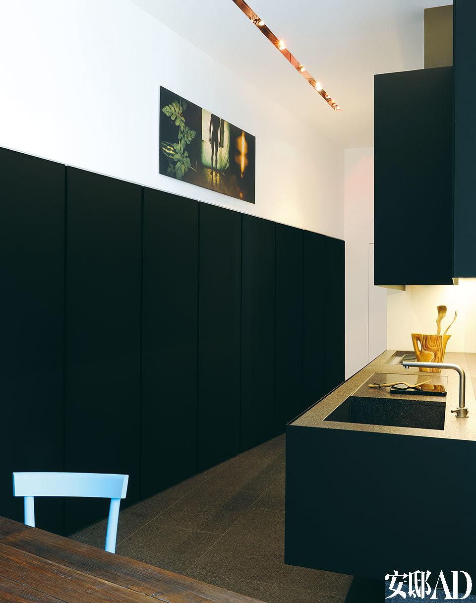 整面墙的黑色壁橱,大胆而艺术的设计,从没见过这么酷的厨房! Minotti的厨房设备,材质是磨光的不锈钢。地板为Valtellina花岗岩,颜色会随着光线从紫罗兰变为深灰色。操作台上放着上世纪50年代的花瓶,有一种木制的效果,它是基于毕加索的一幅素描设计而成的。Kyle Bradfield的摄影作品挂在墙上。嵌入式顶灯来自Viabizzuno。