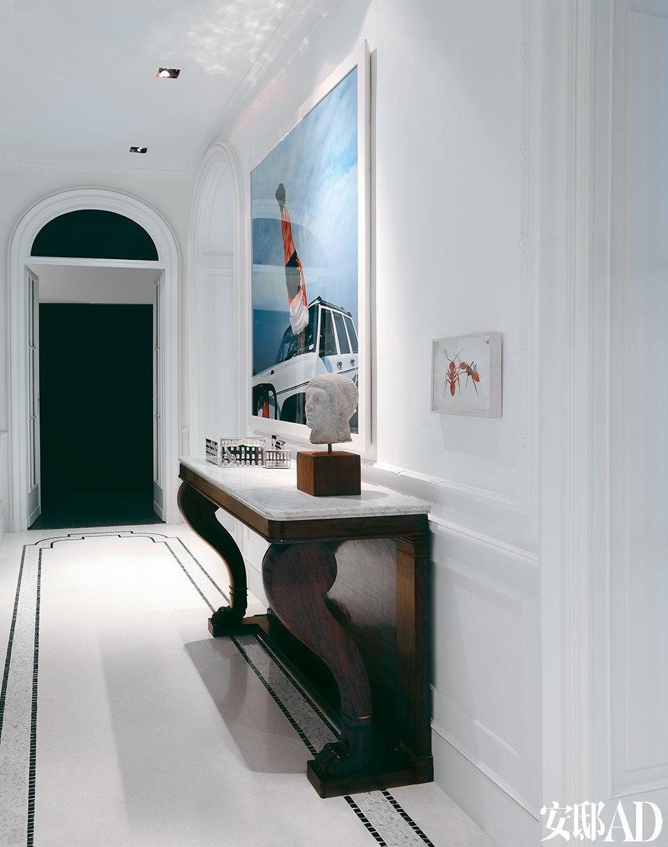 门厅除了黑白色小格的地板外还有一张桌案,是来自Luca家族的物品。墙上的摄影作品来自中国艺术家李炜。