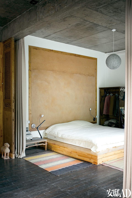 """卧室中刻意用木框装饰出一面土墙,它由号称""""三宝经典材料""""的景德镇釉泥糊成。"""
