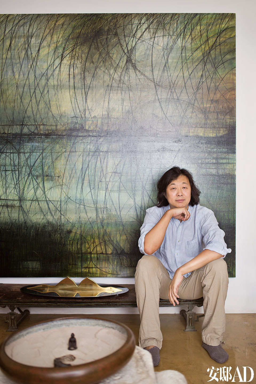 主人:卜镝,生于1970年,自幼随父习画,热衷于中国传统文化及艺术,特别是对佛教美术的学习、研究和收集。中国古代文人的审美理想对卜镝产生了深远的 影响。近几年,卜镝更专注于将自己对东方文化及艺术的理解及感悟用架上绘画的形式创作表现出来。卜镝坐在自己的油画作品前,身旁是他的铜质雕塑作品。