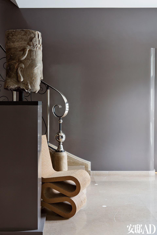 楼梯口布置着公元10世纪的佛头,以及一把Frank Gehry的设计名椅,古老的艺术与摩登的设计,像一对交谈中的好朋友。入口处,佛头雕像来自10世纪。椅子来自Frank Gehry。灰色墙壁已被亮色油漆画粉饰