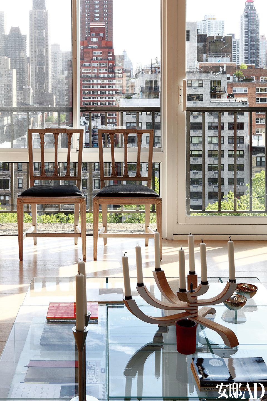 从客厅向外看,两只18世纪的黑色软包木椅并排立在落地窗边,近处的茶几由Piero Lissoni设计,Cassina出品。