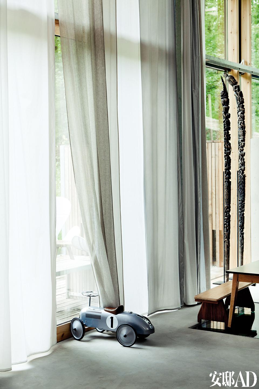 图腾雕塑作门把手,老茶壶组成吊灯,旧汽车竟也能立在墙边当储物柜……天马行空的想象力让这个家绝对与众不同!高大的落地窗让客厅中视野广阔,周边的森林尽收眼底。这个家中尽量保留了物质自然和原始的形态,作为落地门窗框的云雀木(Lark Wood),就取材于周边的树林,本地材料,原汁原味。