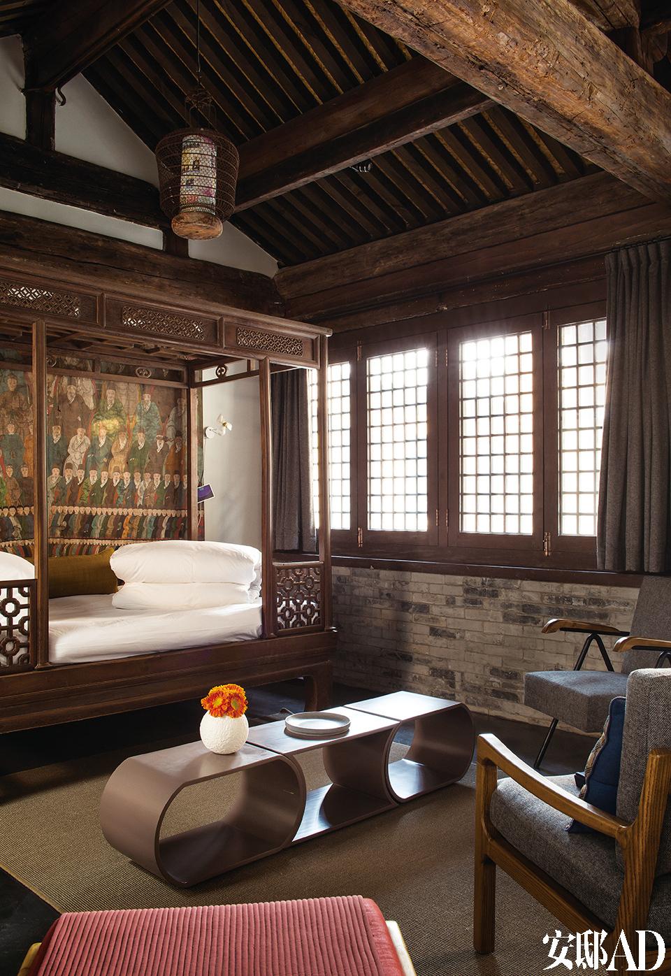 """僧寮客房中唯一的一间单人房""""牡丹""""配备了一张鸡翅木古董雕花床,配上Juan多年前从潘家园淘到的陕西清代家庭画像,更是气场强大。三只凹凸有致的子母桌由刘利年设计,羊毛覆面的扶手椅是Juan请一位上海做家具的朋友定制的。"""