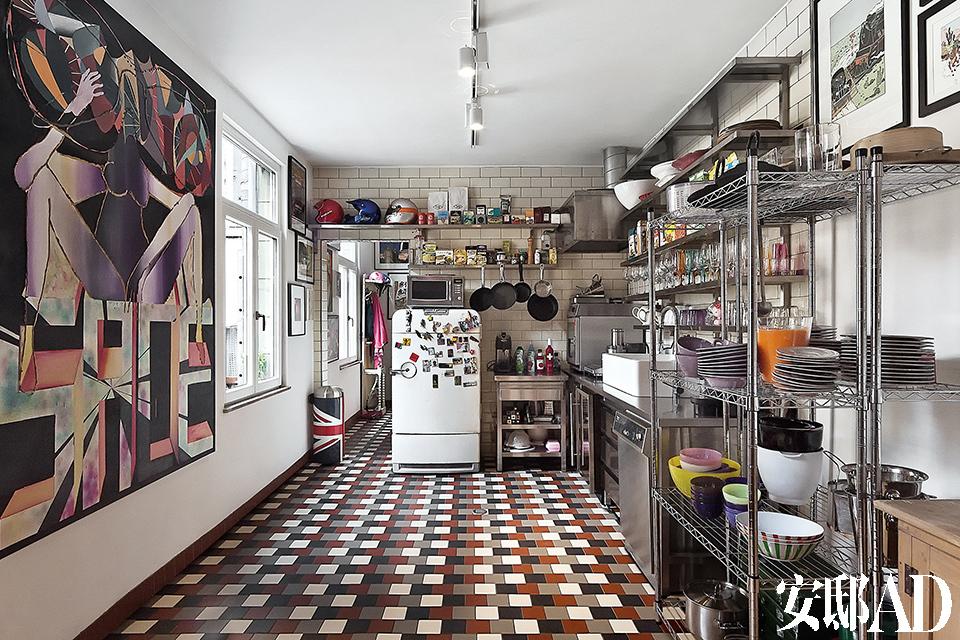 开放式厨房里装备着工艺精湛的Miele不锈钢橱柜,工业感十足,还有一台复古的Chrysler冰箱。地面铺设的四色瓷砖来自法国生产商 Winckelmans,墙面则用了英国Country Tiles生产的奶油色光面瓷砖Metro,两种产品均来自Inter-Ceram。天花板上安装了比利时的Orbit的轨道照明系统,来自布鲁塞尔的 King's商店。墙壁上的油画《SoniaVersace IV》由Aline Bouvy 和John Gillis联手创作。