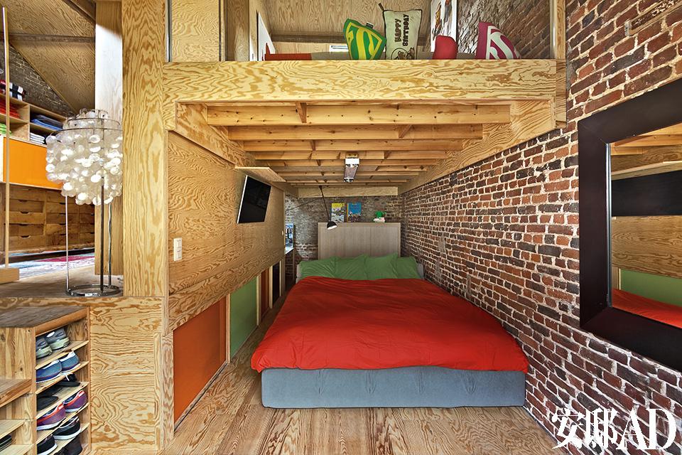 主人的卧室同样应用了木质嵌板以及带彩色推拉门的储物柜。