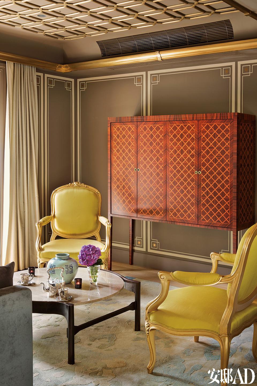 """家族传代的古董家具和精工装饰是整个家的""""镇宅之宝"""",这种时间与气韵的传承绝非金钱可比。主起居的空间经过了精心的分区,以适应大型聚会的需要。古董家具和一座精致的镶花细工壁橱立足于量身定制的长毛绒太平地毯上,成为主起居室的美丽一角。"""