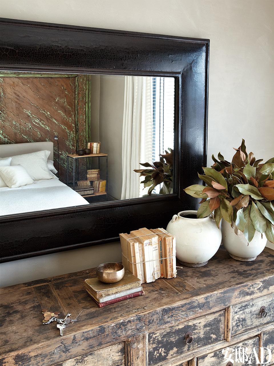 主卧室里搭配了中式黑色漆框镜和中式白陶罐。
