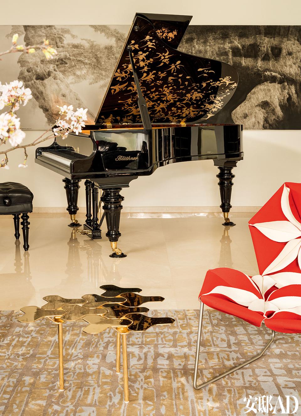 钢琴上的金色漆画呼应着现代造型的小茶几,音乐与设计在这个家中相互交融。客厅的另一侧摆着 Blüthner的Julius大师版钢琴,钢琴后面的画作由雪松创作。