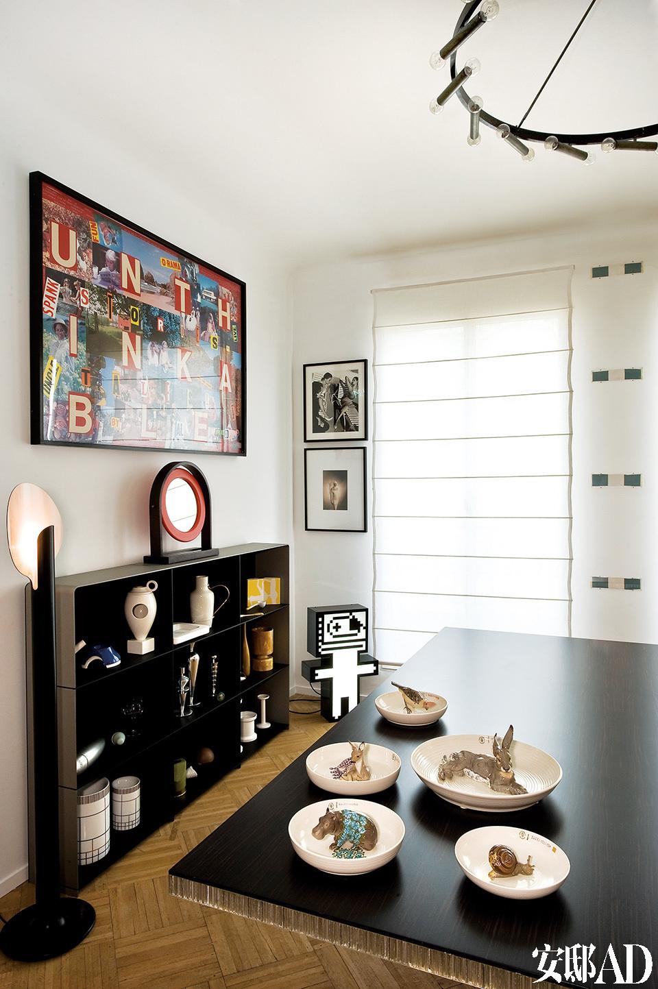 围绕着黑色餐桌,餐厅周围大大小小的艺术品、设计品数不胜数。餐桌上放着德国宁芬堡的陶器摆件,由Hella Jongerius创作。落地灯来自Pierre Paulin,由Martin Szekely设计的搁架上摆满了Jasper Morrison创作的花瓶。上面的小镜子由EttoreSottsass设计,大幅拼贴画也由Allen Ruppersberg创作。窗边挂着Daniel Buren的作品,下方的灯具雕塑由M&M出品。