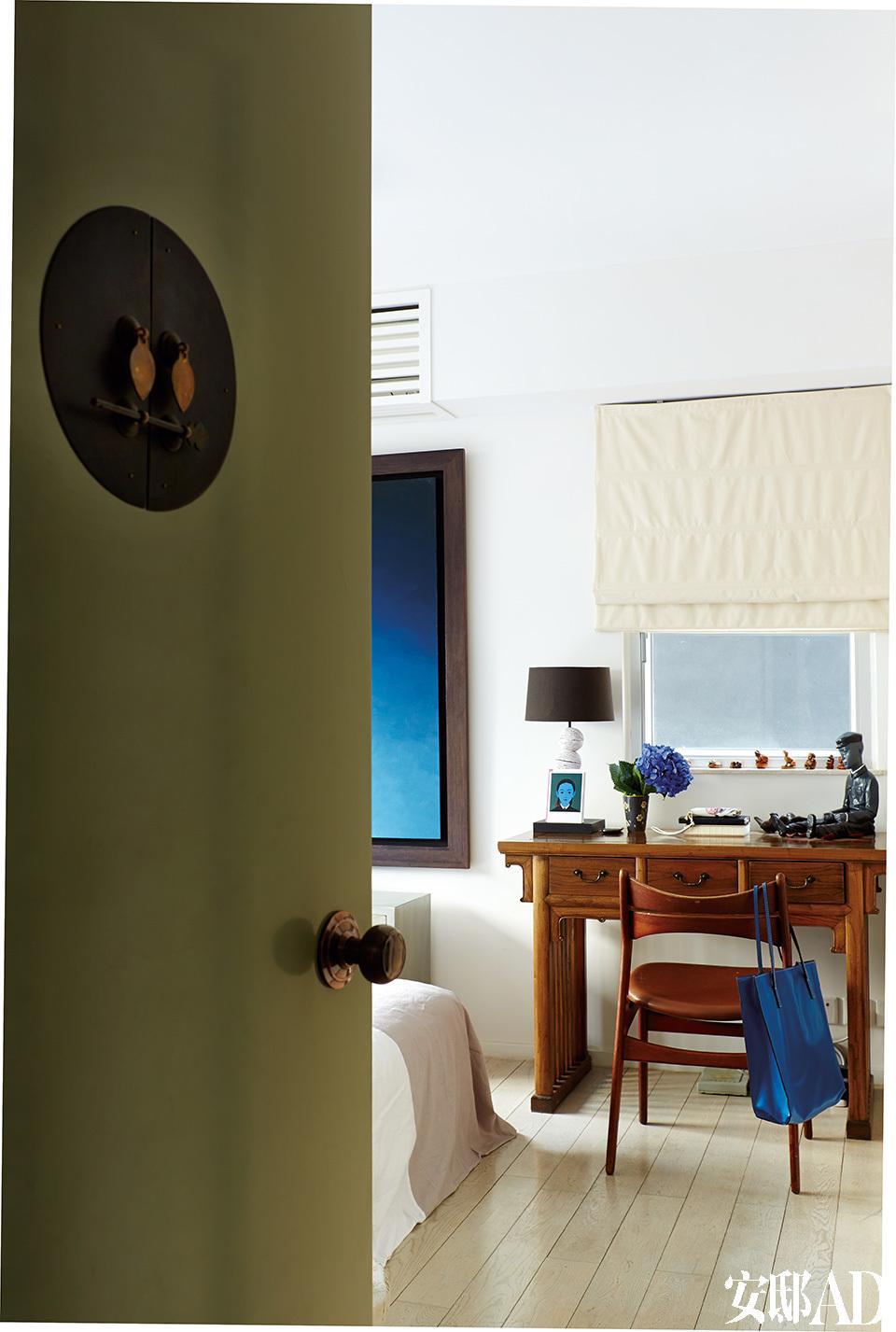 """卧室的门被漆成了调皮的橄榄绿色,装饰性的传统中式门环是点睛之笔。中式古董桌身兼梳妆台和展示柜的双重作用,也是有效利用空间的又一范例。"""" 真正的奢华是能有家的感觉,住在能满足你需要的地方。"""""""