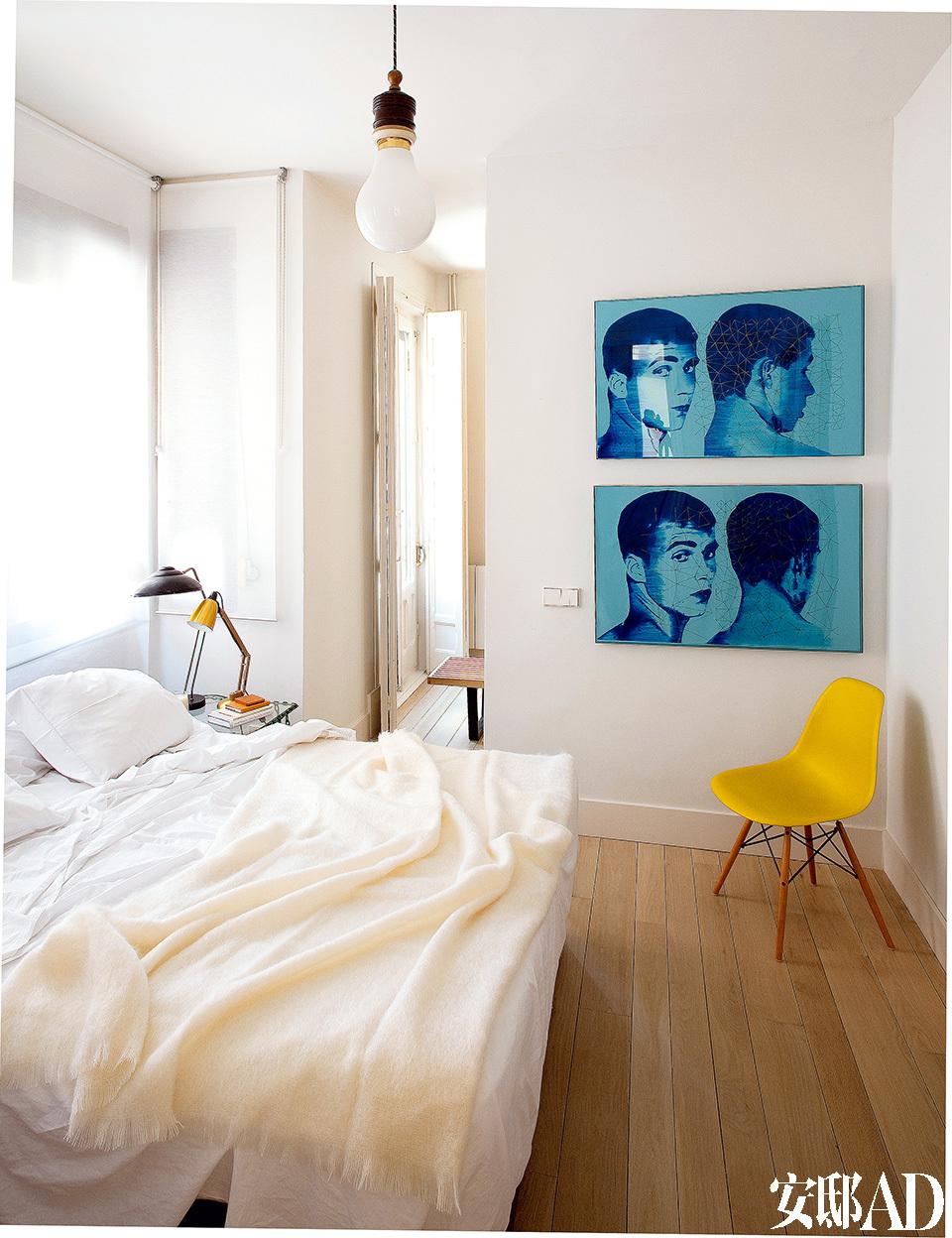 """卧室中挂着Salvador Cidrás的蓝色透明塑料画作""""两次转头""""(Dos Veces Giro),购买于Casado Santapau画廊。Eames夫妇为Vitra设计的DSW椅立在墙角,床罩和马海毛被购于Matarranz,床头桌上放置着Amapola的镀金 可弯曲台灯,""""电灯泡""""(Bombilla)吊灯来自El Rastro。"""