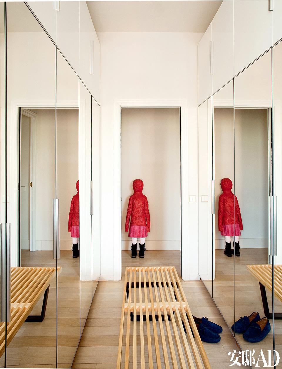 """本来中规中矩的衣帽间,有了"""" 小红帽""""雕塑的背影一下子变得鬼马起来。更衣室里安装了宜家家居的带镜衣柜,长椅是George Nelson为Vitra设计的。"""