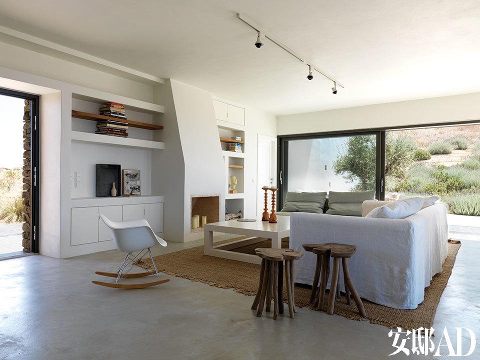 纯手工打造的木头座椅与麦色地毯,为浅白色客厅增添了温暖质感。处于房屋中心位置的客厅,窗外是美丽的山景与海景。白色Caravan沙发来自Mavriki&Co.,定制咖啡桌由Anna -Maria Coscoros设计,古朴的多腿木凳来自Sempre。白色扶手椅是Eames夫妇的经典设计,来自Vitra。