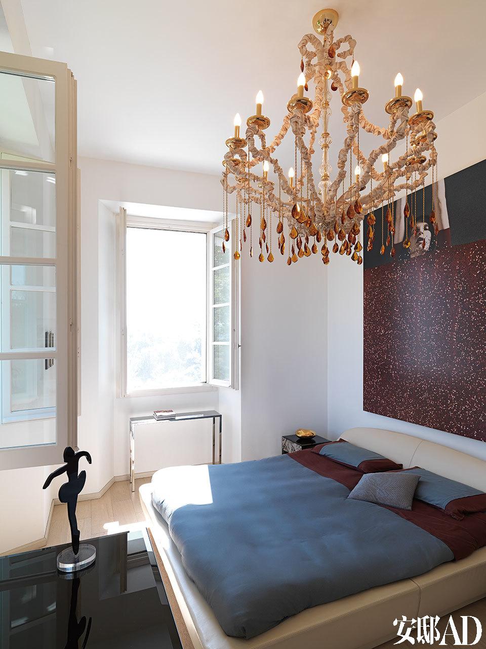 一间卧室中,Big Sleep双人床由Roberto Lazzeroni设计,枝形吊灯Mizar由SamueleMazza设计。 楼上的卧室总是充满阳光,颇具个性的艺术品令空间更与众不同。