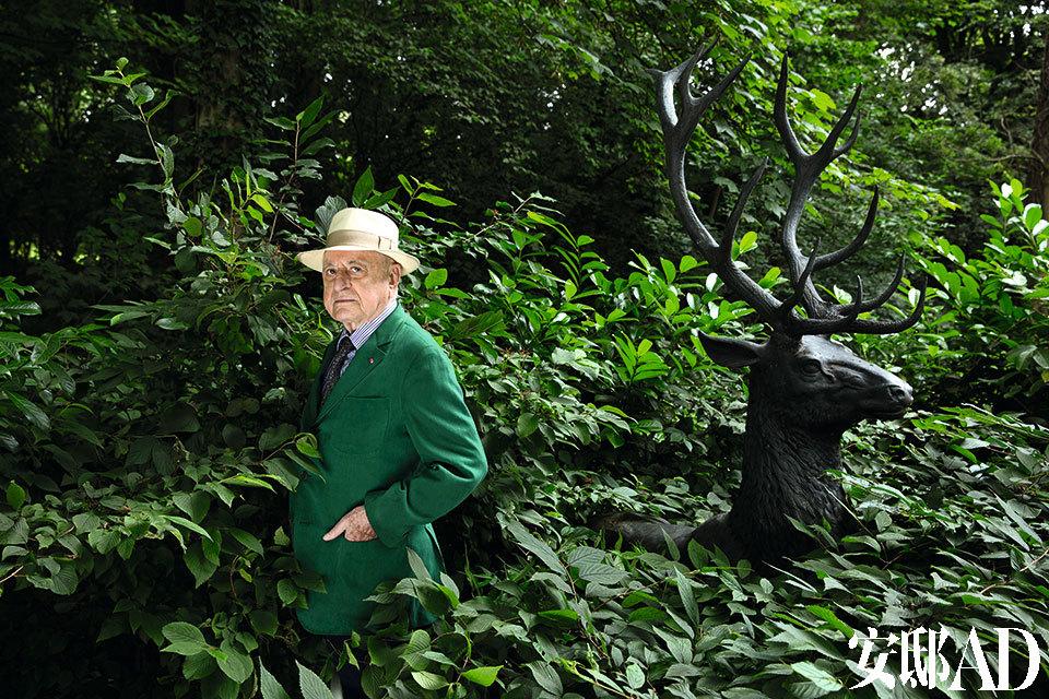 皮埃尔·伯格站在La Datcha花园里一头19世纪的铸铁牡鹿雕塑前,这是他在法国诺曼底海岸的乡间住宅。Jacques Grange设计了这座结构复杂的住宅并负责室内装饰,而Madison Cox Assoc则负责打理花园景观。