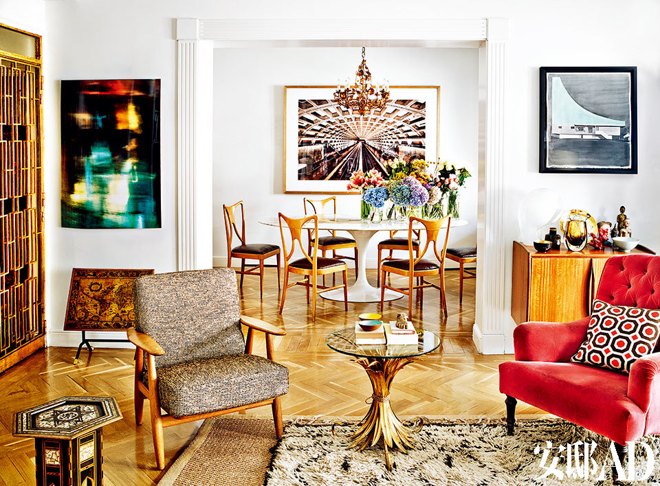 """"""" 我在20年前买下这个房子,' 她'一直不断地被给予小润色、小修改,所以新鲜常在。""""客厅和餐厅相连。左侧金色的门边上是Juan Guillermo Escobar的摄影作品和一张上世纪50年代西班牙地图图案的镀金小桌。右侧是一张Tiempos Modernos的丹麦餐具柜,上面摆着一盏在EL 8购买的穆拉诺玻璃台灯、Fornasetti的盘子和一些部落雕刻。柜子上方挂着在Casado Santapau购买的Alexander Arrechea的水彩画作品。前面是一张Gastón Y Daniela的玫瑰红天鹅绒扶手椅,上面摆着Jonathan Adler的靠垫。椅子左边是一张在EL 8购买的Maison Bagués风格的镀金麦穗状边桌。"""