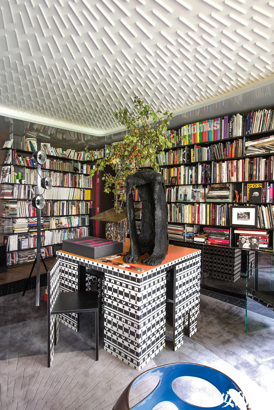 """天花板的石膏表面上贴了大约2500根小木棍,不仅构建出独树一帜的图案,还能利用间接照明的光学效应,产生升高天花板的视觉效果。桌上的青铜雕塑""""Torse Concave N° 3/6"""",由Robert Couturier创作,来自巴黎的Galerie Downtown画廊。"""