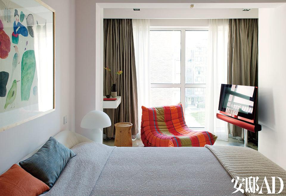 主卧室中,靠窗一侧的彩色休闲单人沙发Togo由Michel Ducaroy设计于1973年,来自Ligne Roset写意空间,一旁的木质坐凳为Poliform品牌,来自家天地,白色Atollo蘑菇灯来自Oluce品牌,电视由荷兰品牌Bang & Olufsen出品。墙上挂的画由王濛莎创作,来自Hi小店(Hi Art Store)。