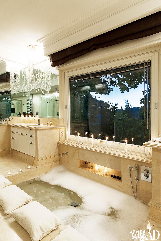 浴室里铺着Delos磨砂大理石,浴池正对落地窗,可以一览窗外绿意葱茏的景色。白色睡枕放在浴池边上,可以让主人泡在温暖浴池里也能小憩片刻。Gessi铬合金的卫浴设备与水晶珠帘吊灯完美地展现了现代与古典的结合。