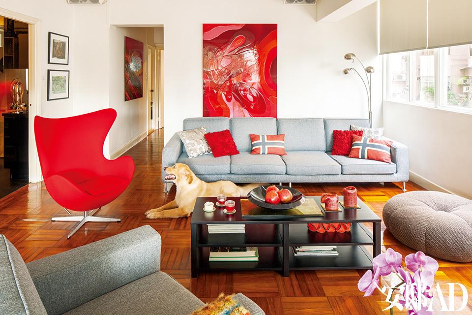 """""""我的作品本身就浓墨重彩, 家里的墙面当然不必再施粉黛啦。"""" 其它那些看似漫不经心的色块铺陈, 其实都是有意而为之。几乎是画出了整套公寓。""""客厅中的一片红彤之下,Gerry在附近定制的超长灰色沙发起到了很好的""""降温""""作用。公寓各处都挂着Gerry自己的画作,这让他在色彩搭配上更加手到擒来。"""
