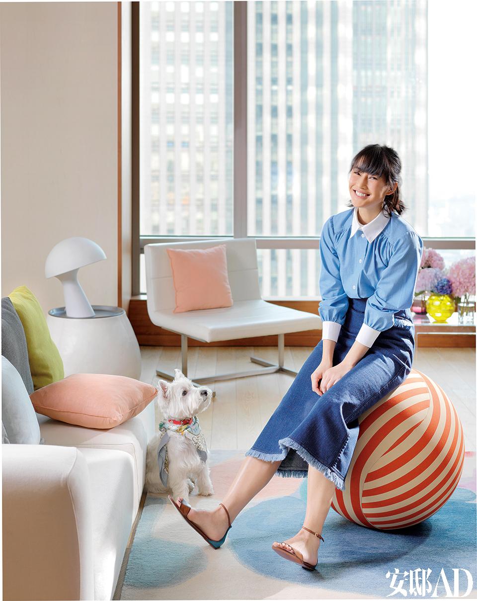 """陈燃坐在客厅的B&B红白条纹沙发脚凳上,名叫""""奥斯卡""""的宠物狗乖巧地守候在她脚边。色彩宛如印象派画作的地毯来自毯言织造,粉色靠枕来自 DOMO,蘑菇灯是北欧风情的。蓝色衬衫、牛仔裙、褐色凉鞋 均为Louis Vuitton。"""