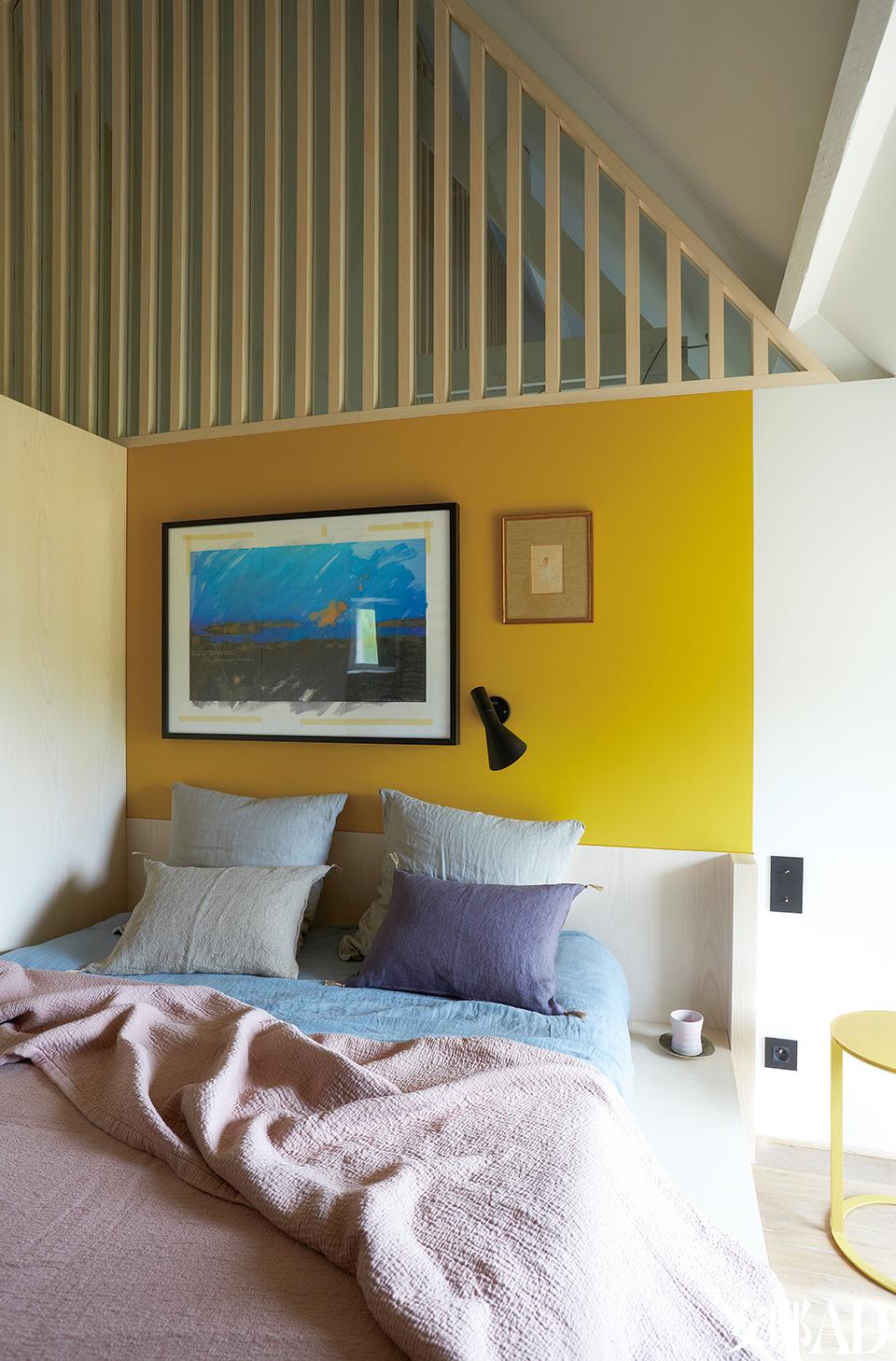近屋顶的木格栅覆盖着玻璃罩,让自然光线得以充满整个房间,又与隔壁的儿童房相互隔音。主卧室中,床头墙面喷涂了明亮的黄色,上方的木质格栅覆盖着玻璃。定制大床上的床品和靠垫来自Caravane,购自Saint-Malo的La Maison Générale。床边AntonioCitterio设计的边桌Frank来自B&BItalia,壁灯AJ50是Arne Jacobsen的作品,由Louis Poulsen出品,墙上的油画同样来自主人Guillaume。