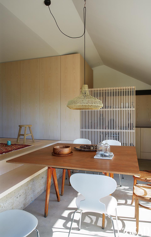 客厅与餐厅之间的地面具有高差,设计师索性将连接处变成了混凝土和木板组成的绝佳长凳,木格栅遮挡着一间开放式厨房。