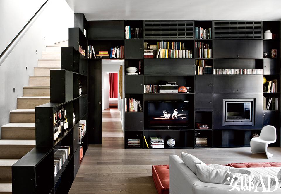 """起居室,黑铁制成的书柜,由两种不同尺寸的模块拼装而成,是Jacopo 2007年的设计,它不仅仅是书柜,还身兼货柜、栏杆、电视柜、空调柜等职能。右侧有把可爱的白色""""Panton Junior""""椅。 家中所有家具设计都充分挖掘了工业材料的简约感,并以功能性作为出发点,书柜还身兼电视柜、空调柜、储物柜、楼梯栏杆等功能。"""