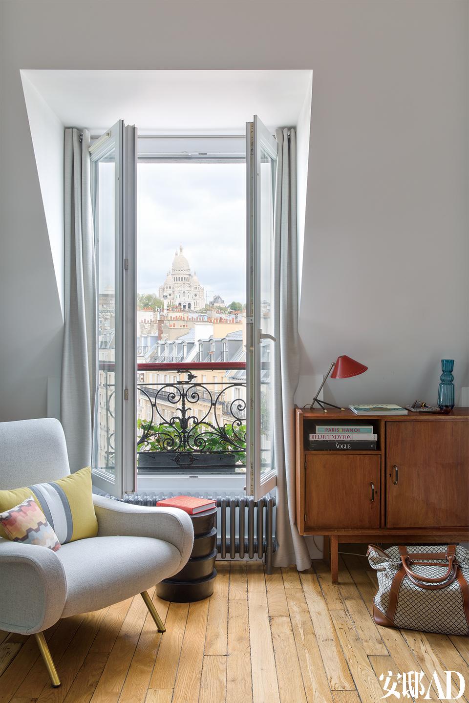 卧室正对着一扇窗,右侧一张20世纪50年代的胡桃木柜来自巴黎的跳蚤市场,柜面上一只Pinocchio红色台灯由H. Busquet在1953年为Hala设计,木柜前的地面上放着主人的Gucci旅行包。