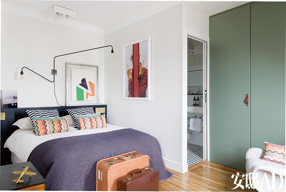床上的黑白格靠垫购自The Conran Shop,橘色靠垫为Missoni Home品牌,灰色床单则来自Habitat。床头灯购自巴黎的跳蚤市场,墙上红色摄影作品是Patrick Chelli在2012年拍摄的《TerryRichardson》,绿、黑、橘三色拼贴艺术品来自Guy de Rougemont。橄榄绿色的衣柜门里,不仅放置着主人的衣物,还完美隐藏了洗衣机、热水器以及整个家的电路控制板。