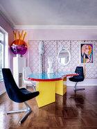 """大胆奔放的配色和品位独 特的艺术品选择,是Jenny-lyn的标志,它们冲破了原本建筑结构的阻碍,令这个家焕然新生。餐椅是上世纪60年代的Unicorn Chairs,来自Chromcraft Sculpta,桌子后方是上世纪70年代的塑胶橘紫色雕塑,艳丽的色彩与自由的造型十分惹人注目,它的名字叫""""bong"""",由Mario Benedetti设计。餐桌上摆放的人头雕塑品实际上是陶瓷花瓶,由艺术家Oriel Harwood设计。挂在墙上的椭圆形镜子是一位来自伦敦的艺术家的作品。"""