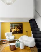 """客厅里,在AdrienMissika的《StandingWaves 01》摄影作品(Bugada & Cargnel工作室)下放置着Franco Albini设计的""""Tre Pezzi """"扶手椅(来自 Cassina)和Pierre Paulin设计的""""Pumpkin""""长沙发(来自Ligne Roset)。在沙发后面,立着由Barber和Osgerby共同设计的""""Tab F""""阅读灯(来自Flos)。 在Samuel Accoceberry设计的""""Tresse""""地毯(来 自Chevalier)上,还放置着Jaime Hayon设计的""""Collection II""""矮桌。"""